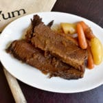 Instant Pot Brisket on white plate with carrots and potatoes and a YUM napkin and fork