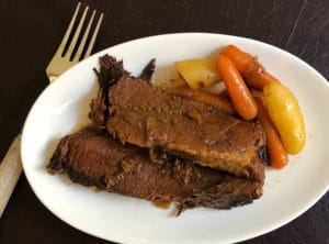 Instant Pot Brisket beauty shot of two slices with carrots and potatoes on a white plate with a fork
