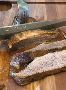 Instant Pot Brisket slicing cooked meat on board to show grain