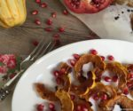 Roasted Delicata Squash with Pomegranate Molasses and Date Syrup on white plate with parchment and pomegranate and squash