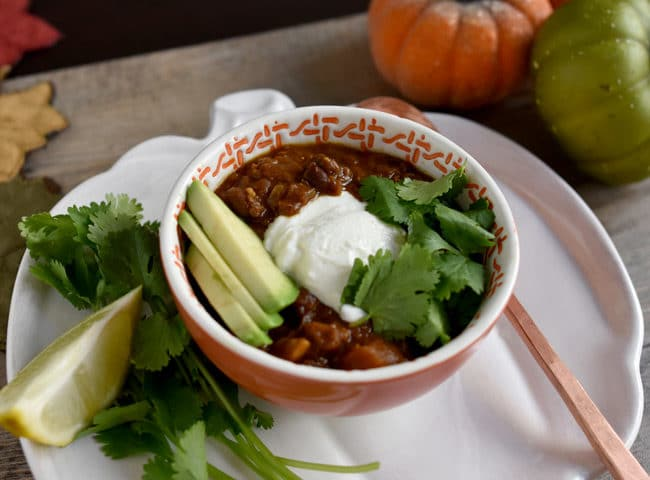 Instant Pot Red Lentil Chili in a bowl at an angle with avocado, cilantro and yogurt on top