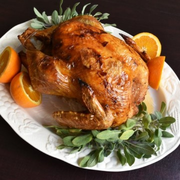 Whole Dry Brine Turkey Roasted on a white plate with fresh sage and oranges
