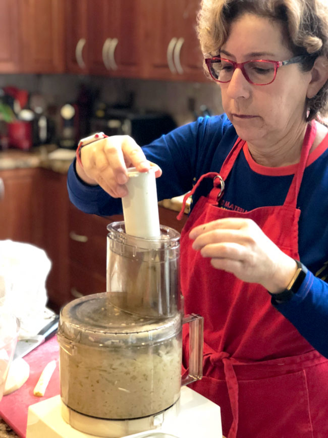 Beth Lee using food process to shred potatoes for latkes