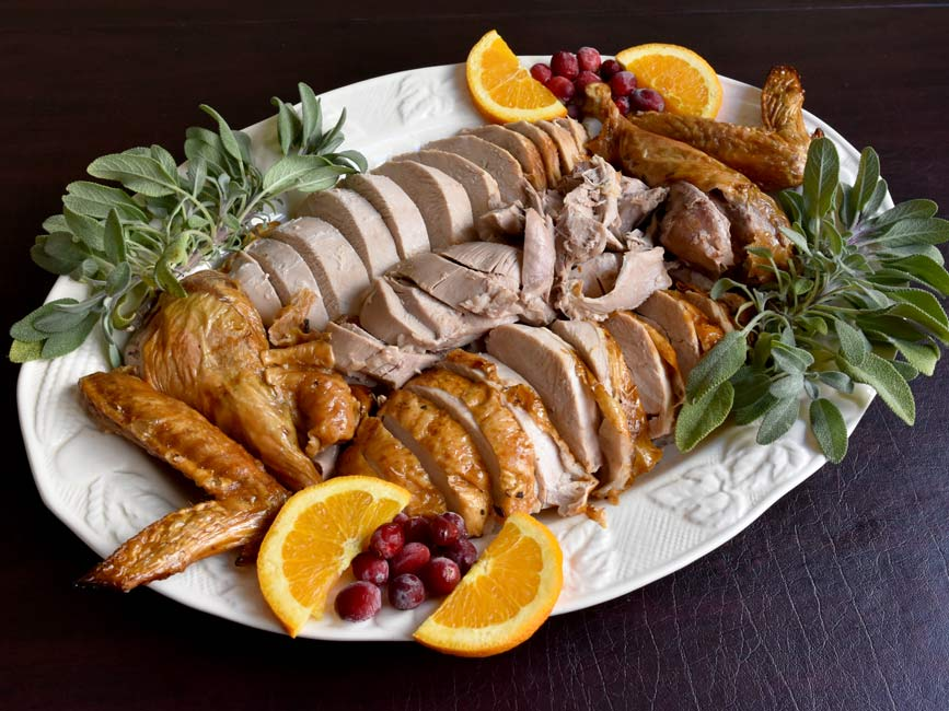 sliced whole turkey on white plate with cranberries and oranges