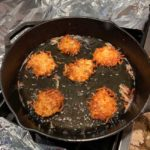 several latkes cooking in cast iron pan