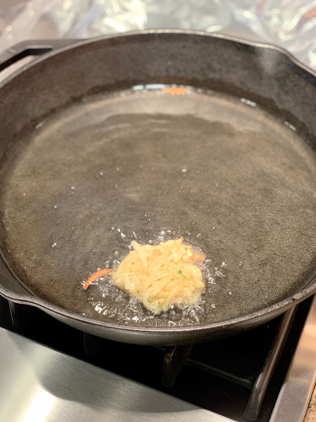 testing one latke to cook in oil in cast iron pan