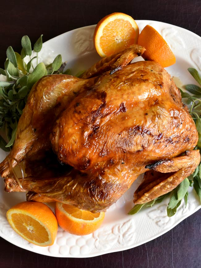 Whole cooked turkey on white plate with orange and sage