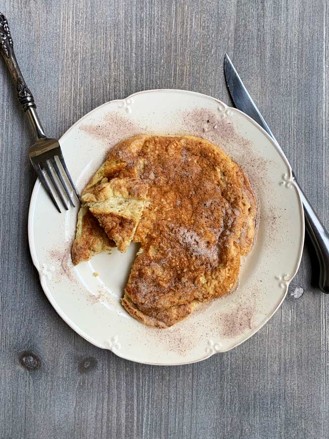 matzo meal pancake with cinnamon sugar on plate with knife and fork