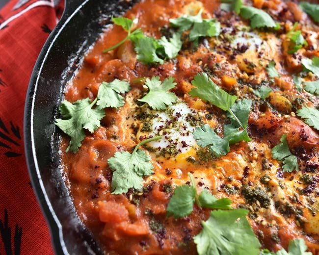partial view of cast iron pan showing za'atar and sumac on egg tomato mixture