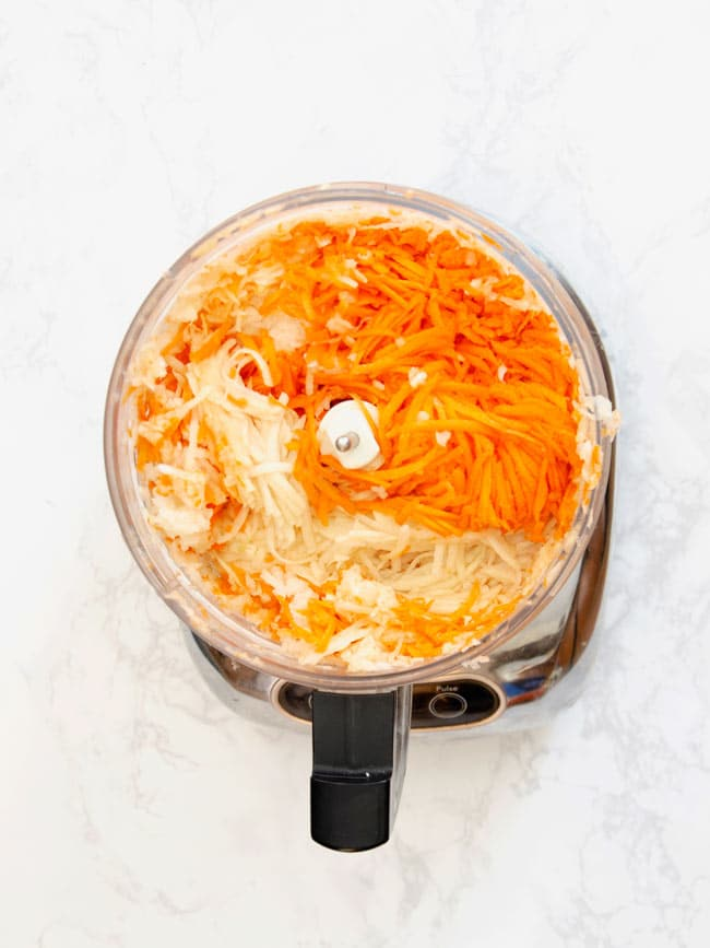 shredded carrots and potatoes in food processor for potato kugel