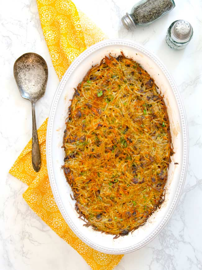 baked potato kugel in white casserole dish with yellow napkin and large serving spoon