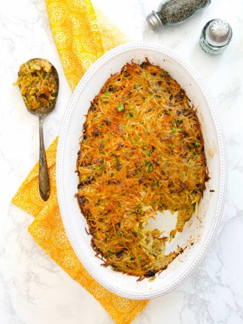 cooked crispy potato kugel in dish with serving spoon of kugel on the side