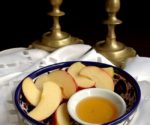 apple honey in bowl with candlesticks in background