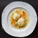matzo ball soup in white bowl on dark brown background