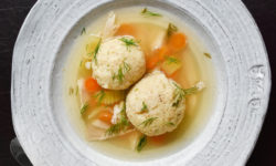 matzo ball soup in white bowl on dark brown background