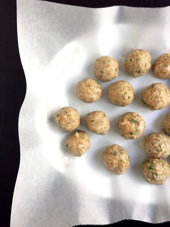 matzo balls uncooked on parchment paper