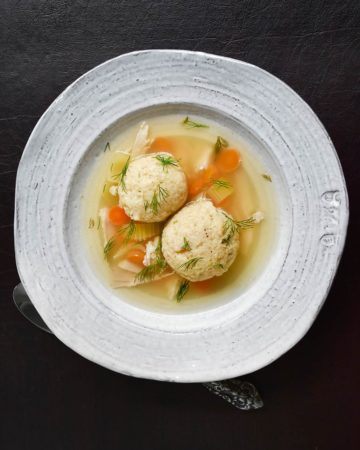 matzo ball soup in white bowl on dark background