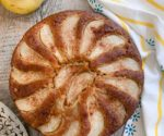 whole pear cake with pear, cake server, striped napkin