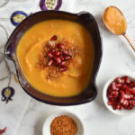 soup in purple bowl with copper spoon and dukkah and arils