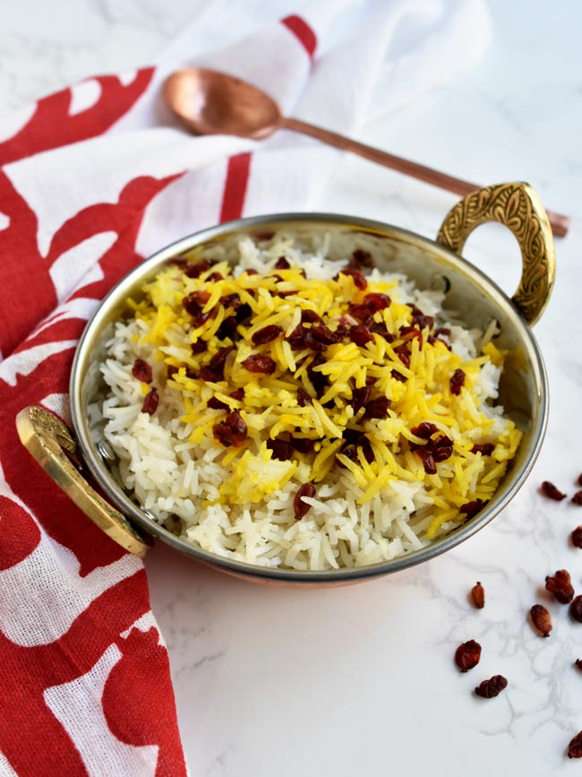 saffron barberry rice in copper bowl with pomegranate napkin and copper spoon