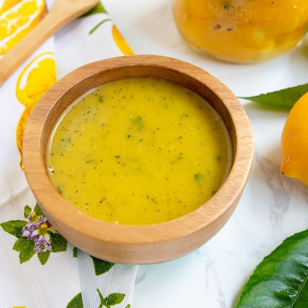 dressing in wooden bowl with preserved lemon jar