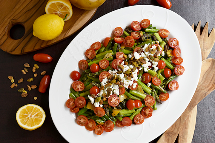 asparagus salad with tomatoes on white plate