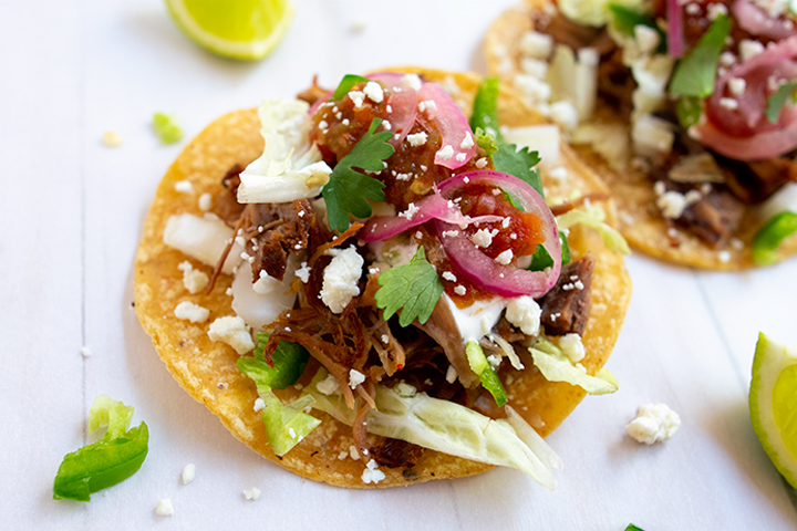 close up of carnitas tacos on white background with limes
