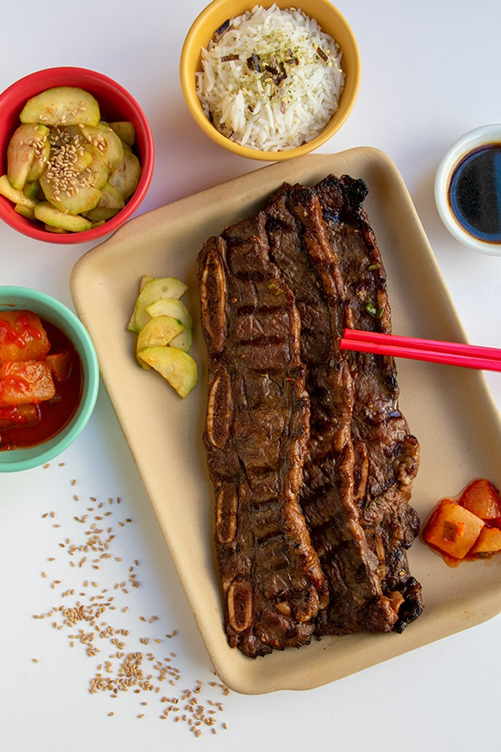 3 korean ribs with side dishes and basting sauce with red chopsticks