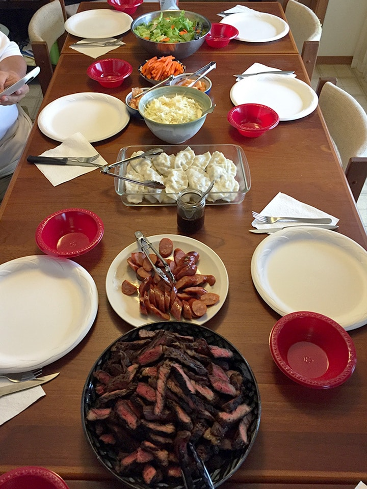 Hawaiian style feast on table showing beef, dumplings, portuguese sausage and salads