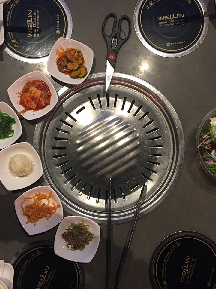 table top shot of a restaurant bbq in a Korean restaurant with side dishes