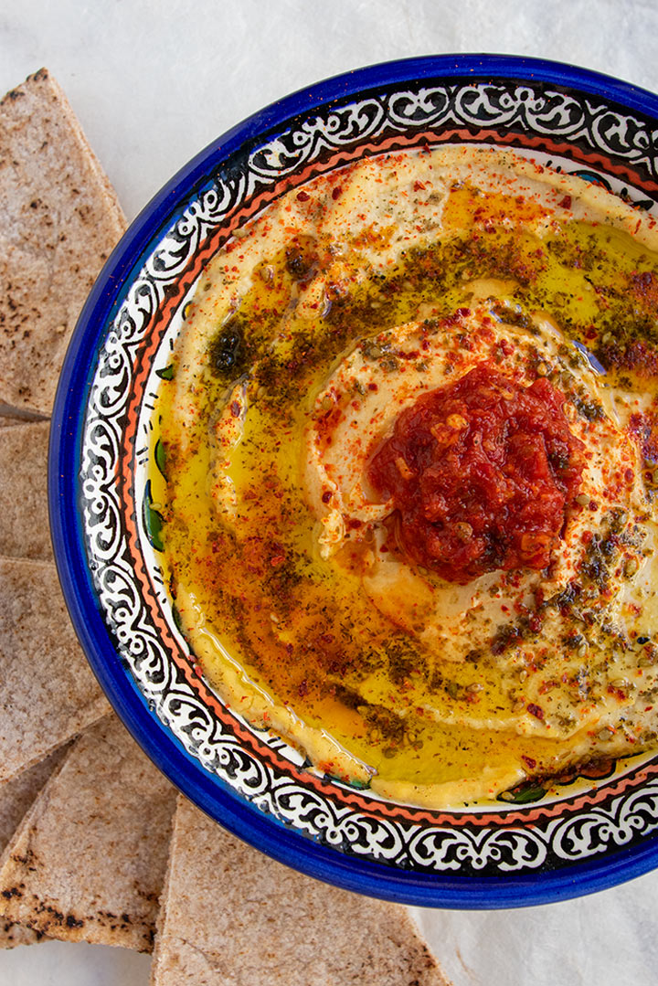 close up view of bowl of preserved lemon hummus with za'atar, marash pepper and harissa on top