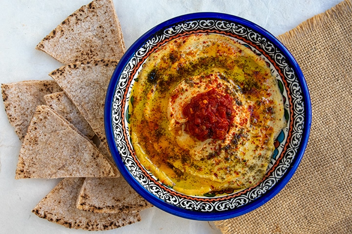 straight down shot of hummus with preserved lemons in blue bowl with pita chips on the left