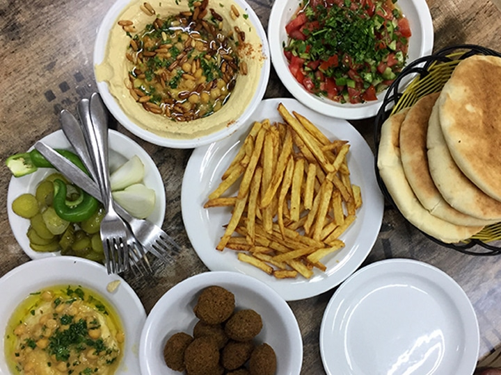 lunch spread of hummus, pickles, chopped salad, pita, falafel and french fries in the Muslim Quarter of the Old City of Jerusalem