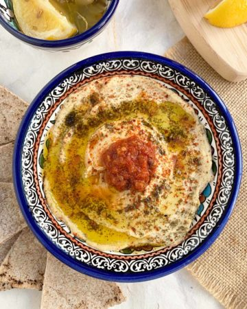 straight down beauty shot of preserved lemon hummus in blue bowl
