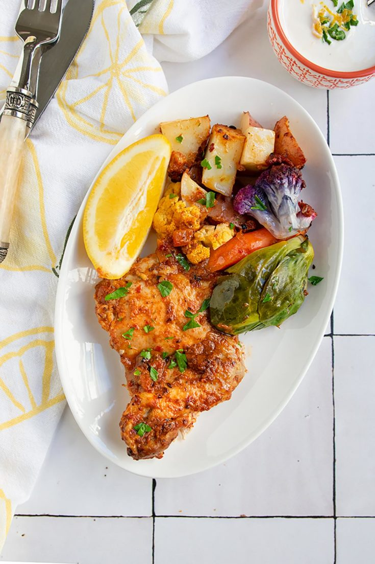 harissa chicken on white plate with vegetables on a tile background
