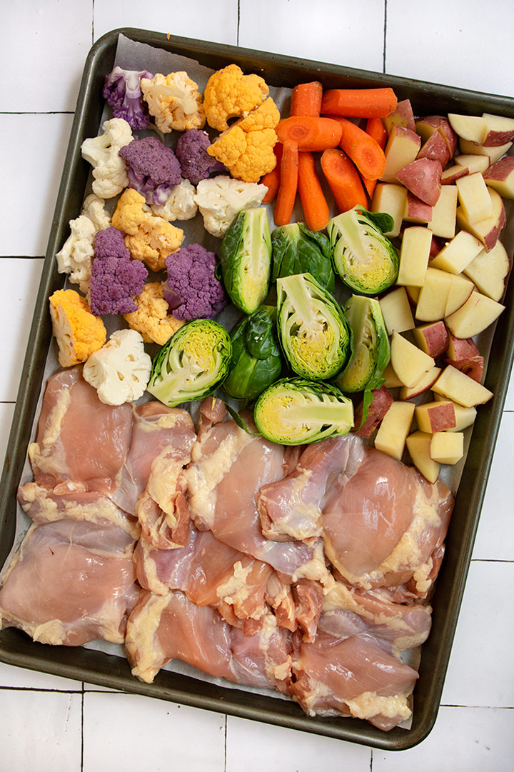 Sheet tray with raw chicken and uncooked vegetables