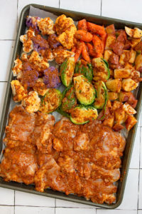 chicken and vegetables brushed with harissa sauce on sheet tray