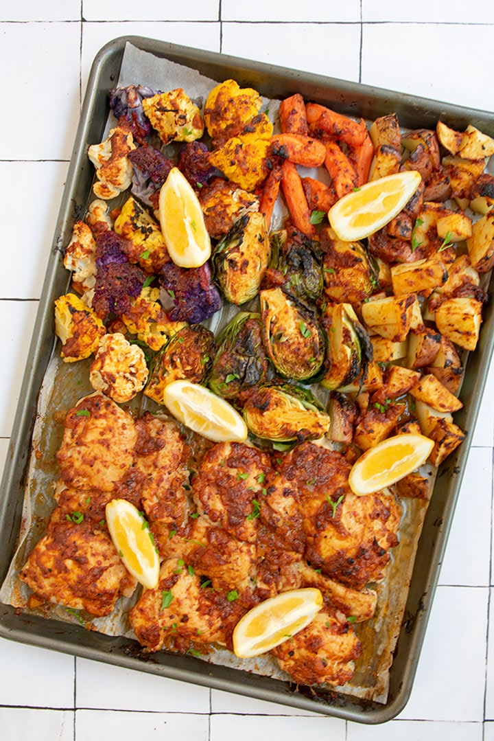 Full tray of cooked harissa chicken with roasted vegetables and some lemons slices on top.