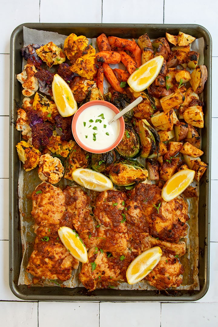 Sheet pan with cooked harissa chicken and vegetables with lemons and yogurt sauce on top