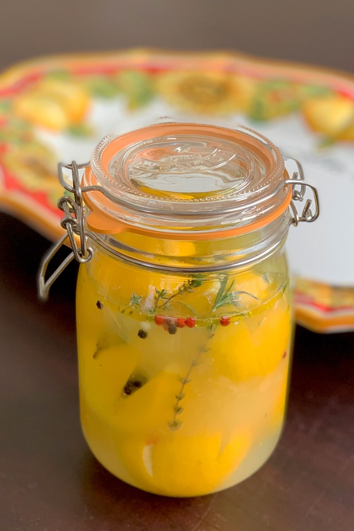 A jar of preserved lemons with lemon plate in the background