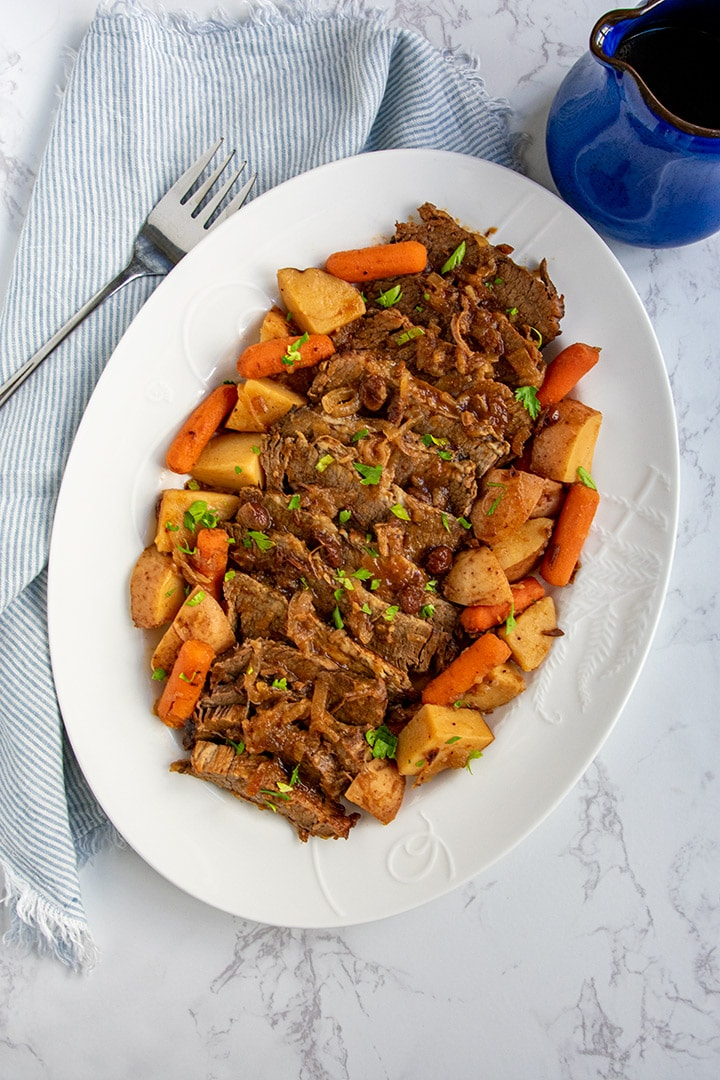 platter of sliced brisket with potatoes and carrots with serving fork and gravy pitcher