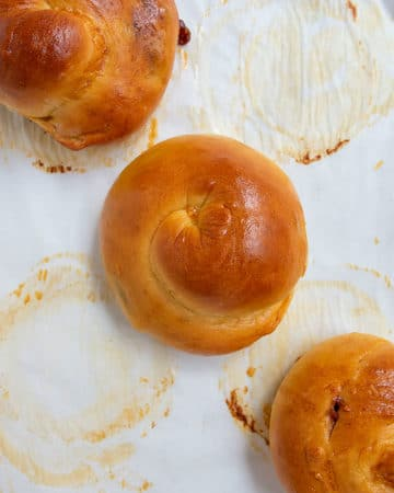 3 challah rolls at an angle on baked parchment paper