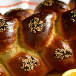 pinterest image showing baked challah with seeds and a sliced orange