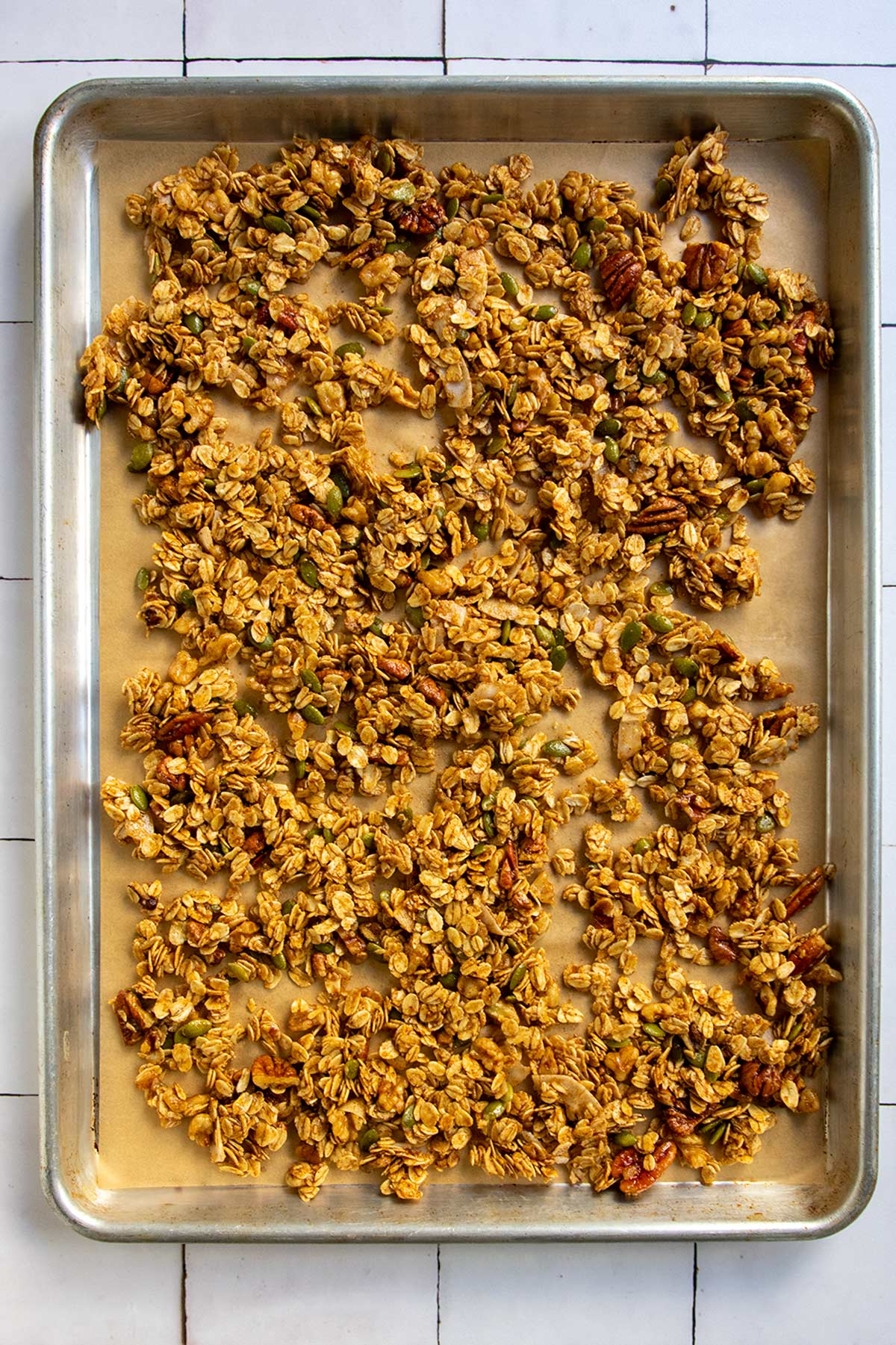 unbaked granola on parchment-lined sheet tray