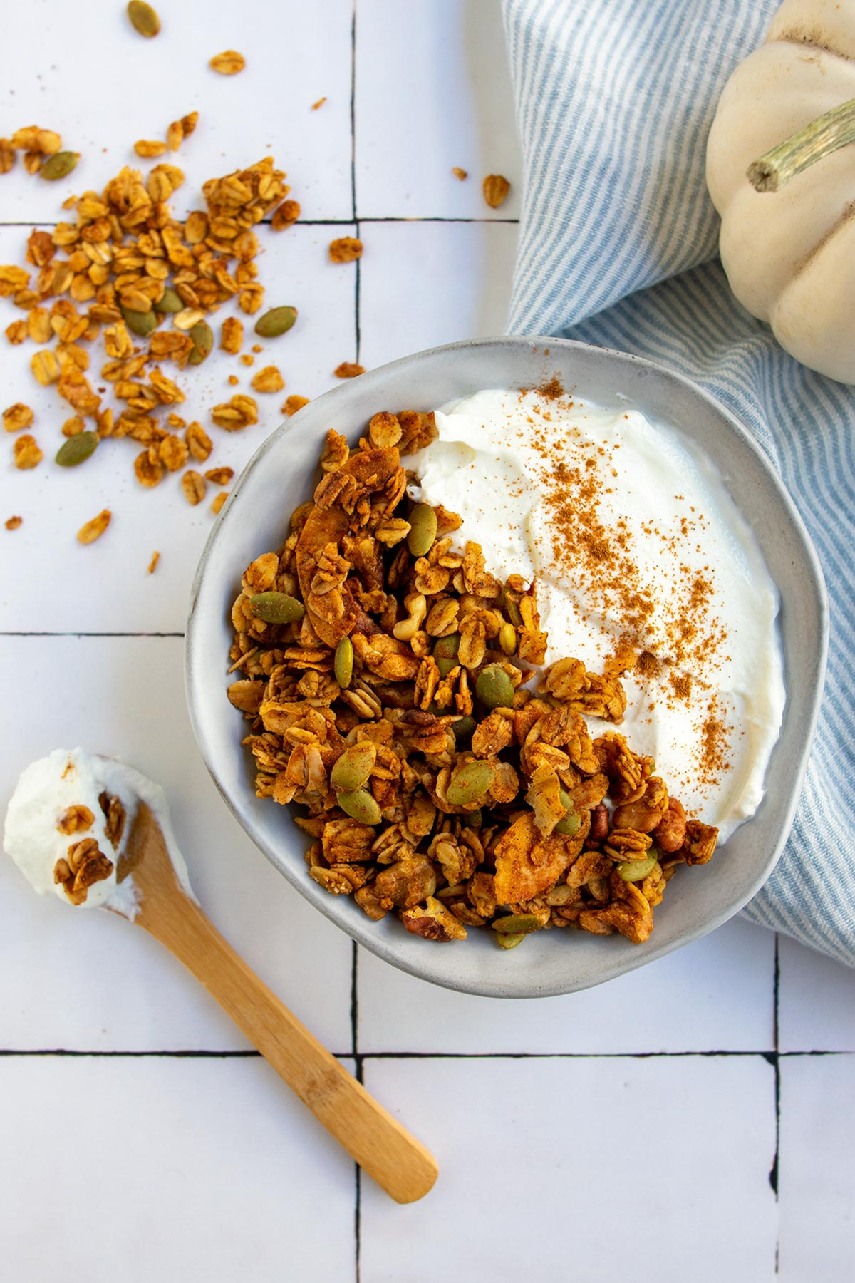 granola in gray bowl with yogurt and cinnamon and a white pumpkin in the side