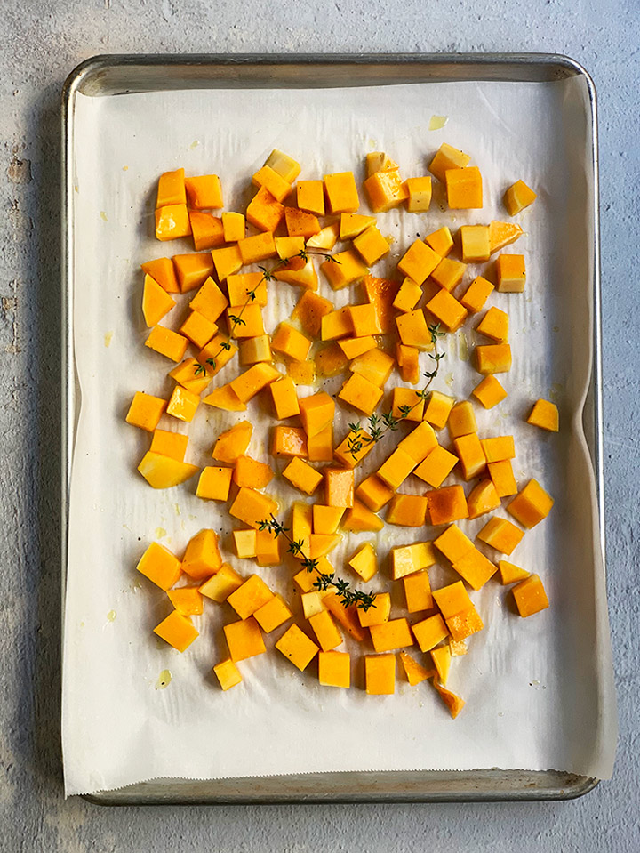 uncooked butternut squash on parchment paper-lined tray