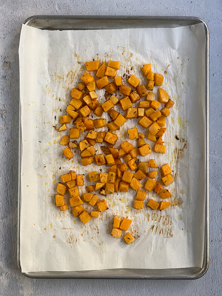 butternut squash cubes cooked on parchment-lined tray