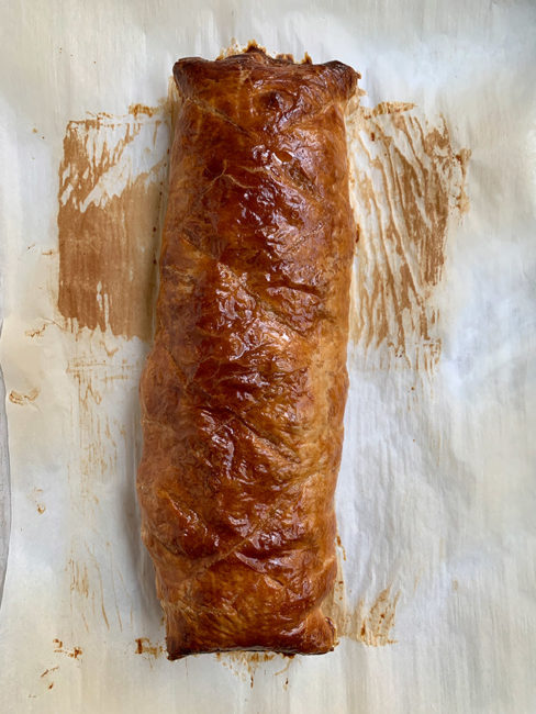 fully baked wellington on baked parchment ready to be sliced