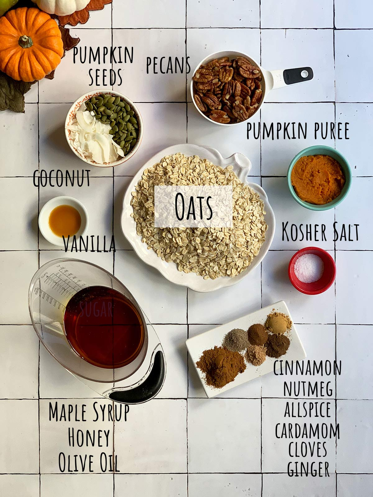 all ingredients for pumpkin pie granola on tile background with labels for each one