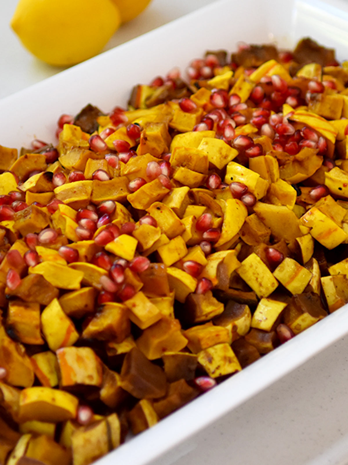 large white plate of cubed cooked delicata squash with pomegranate seeds on top